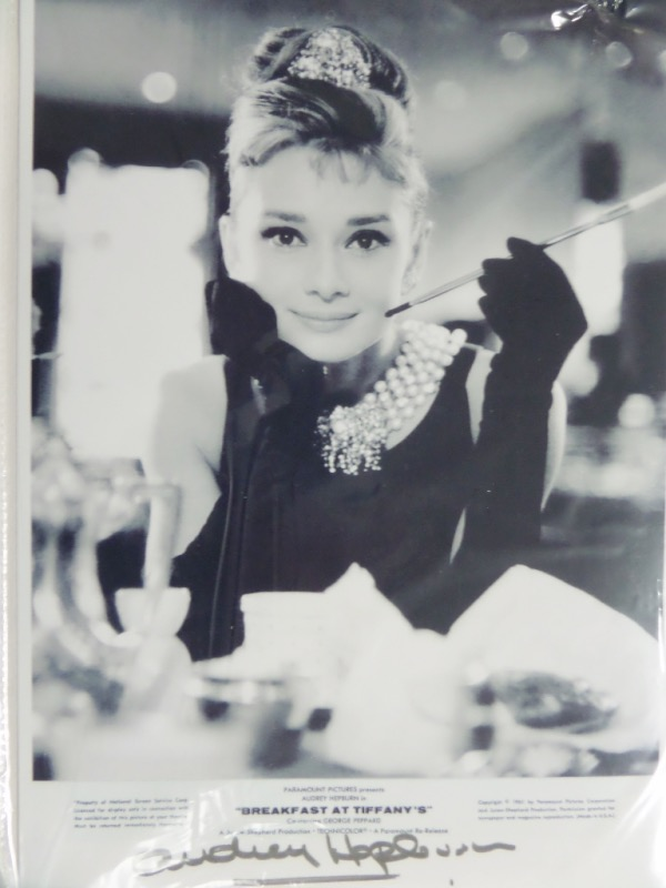 "This black and white photo measures 7.5x11, and is for the 1961 hit movie, ""Breakfast At Tiffany's.""  It is an image of Audrey Hepburn as her Holly Golightly character, and comes hand-signed at the bottom in gold paint pen by the Academy Award winning actress herself.  Valued well into the hundreds!"