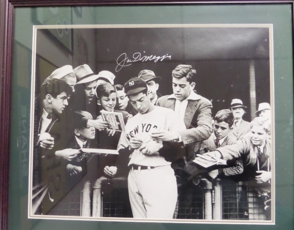 "This gigantic custom wall hanging is a whopping 24x30 in size, and holds a silver paint pen signed B&W image of Joe D. He is swarmed by kids and signing autographs circa 1945, his signature is a 10, as is the free custom double matting and wood framing provided. This piece is gorgeous, and value on this super-sized ""Yankee Clipper"" gem  is above a grand."